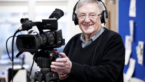 Older man participant using film camera