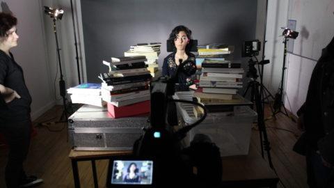 Kiana Kalantar-Hormozi surrounded by piles of books, lights and camera